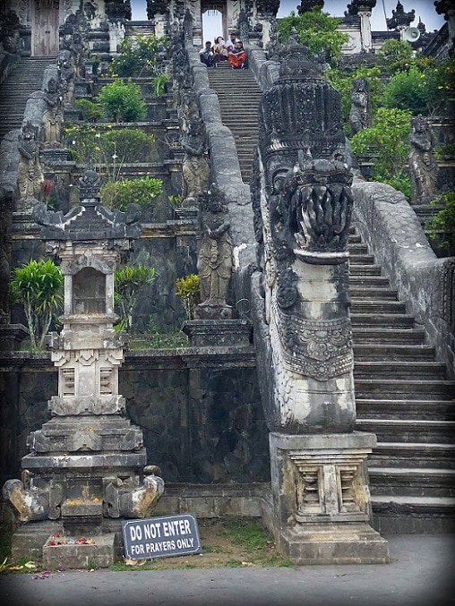 Decorative steps at Pura Lempuyang, home of the Gates of Heaven in Bali. A stone offering stand in the foreground, next to a stone dragon which decorates the front of the steps.