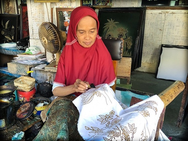 An older Indonesian woman in traditional headscarf prints a batik art pattern with wax on fabric, using a batik writing tool, at a batik making workshop in Yogyakarta, Indonesia.