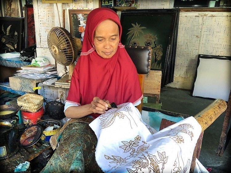 An older Indonesian woman in traditional headscarf prints a batik art pattern with wax on fabric, using a batik writing tool, at a batik making workshop in Yogyakarta, Indonesia.