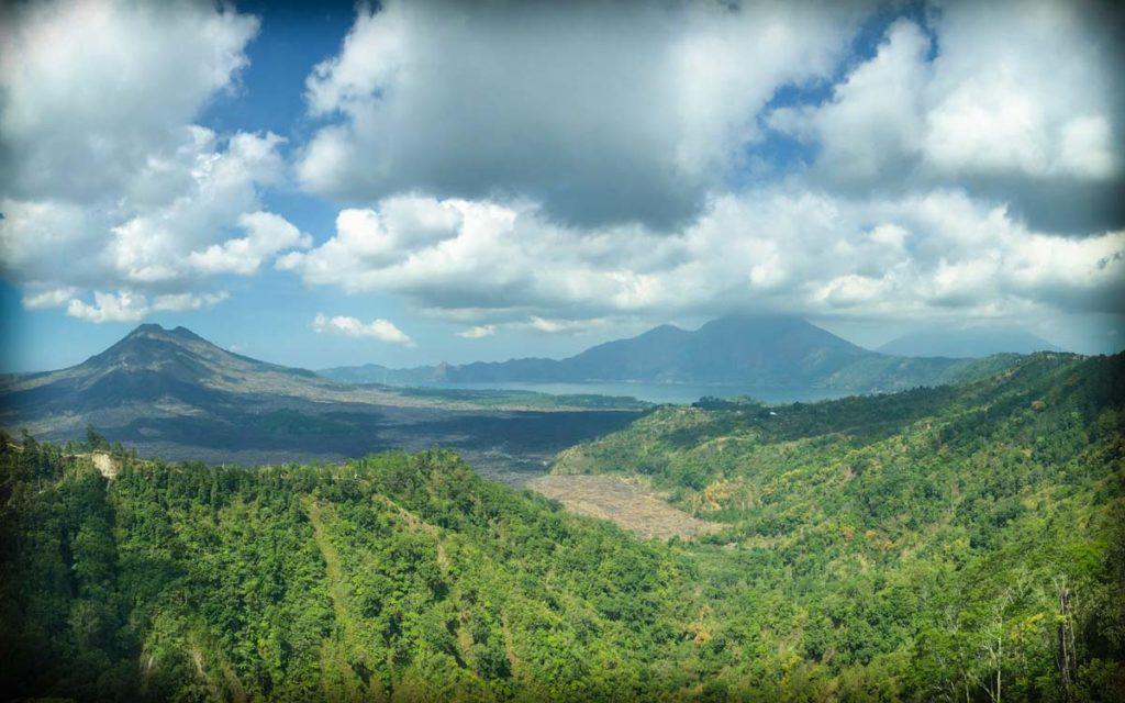 A scene to illustrate Bali facts about the landscape of Bali. Lush green forest in the foreground, with volcanoes in the background. Clouds are in the sky.