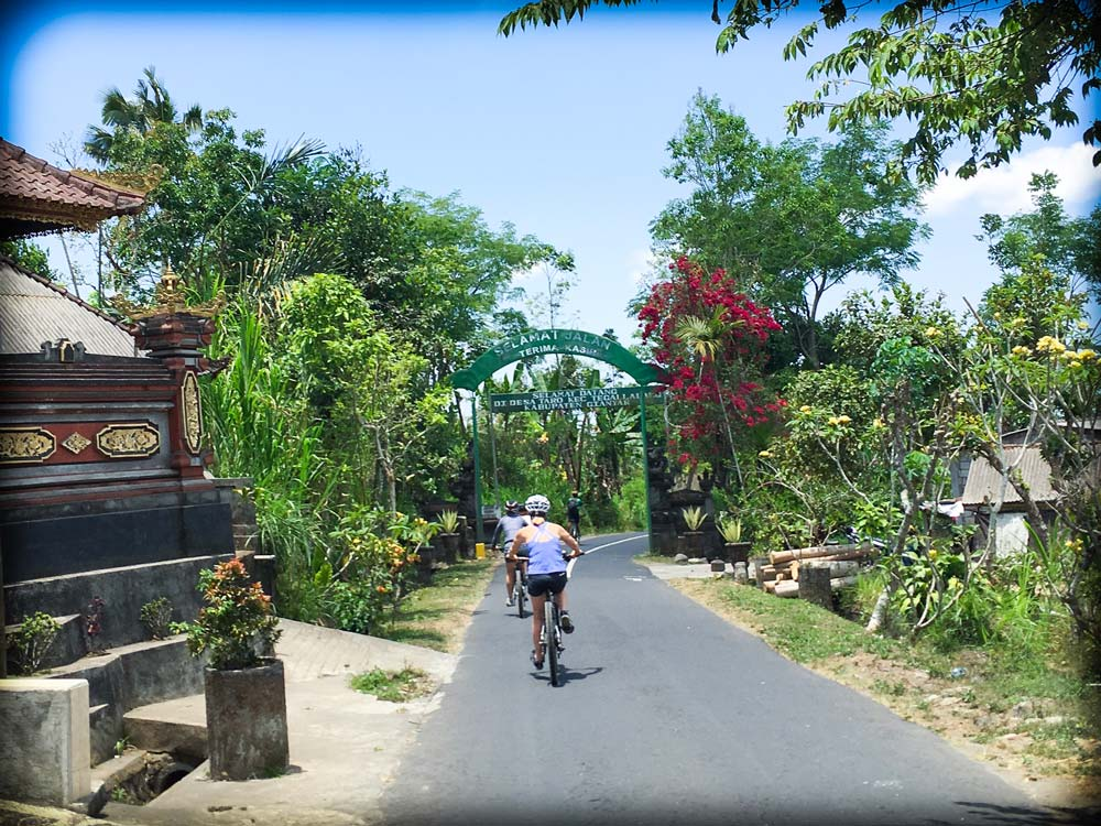 A bicyclist rides along a paved road in Bali, as part of downhill cycling Ubud activities. The bicyclist is biking away from the camera, so we see their back. To the right of the bicyclist are trees and plants, and to the left of the bicyclist is a traditional Balinese building in the foreground, and trees in the background. In front of the bicyclist is an arch across the road with words written on it.