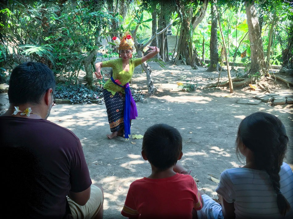 A Balinese dancer performs for a father and two kids during a Bali day tour in a traditional village