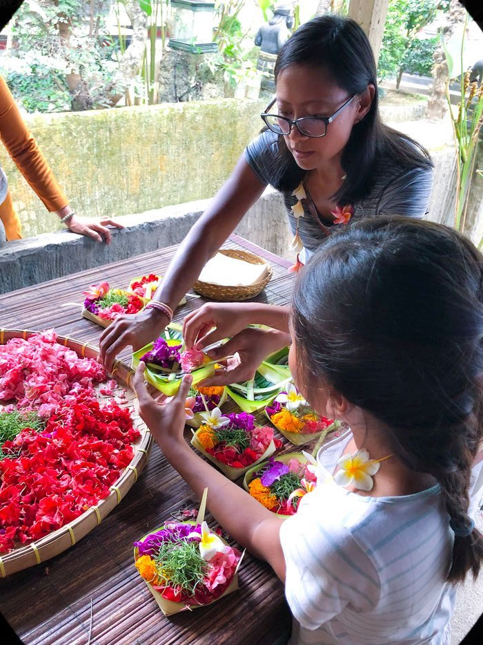 A woman and girl learning to make traditional Balinese offerings during a Bali day tour in Indonesia