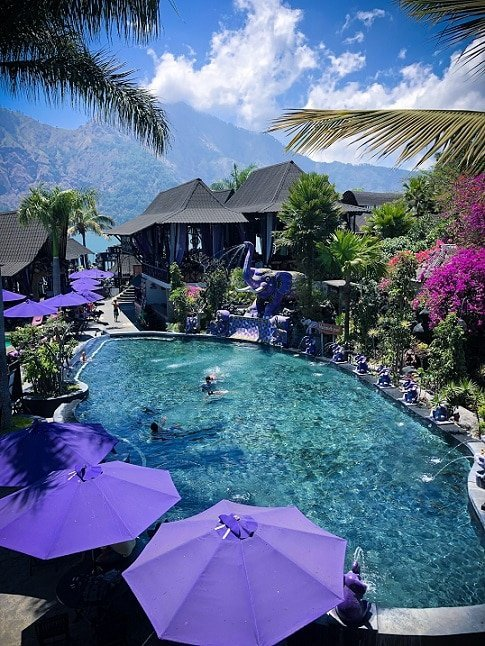 A Bali hot springs pool at Toya Devasya. Purple umbrellas line the left side of the pool. Purple elephant fountains line the right side of the pool, spouting water into the pool. In the background are palm trees and Mount Batur.