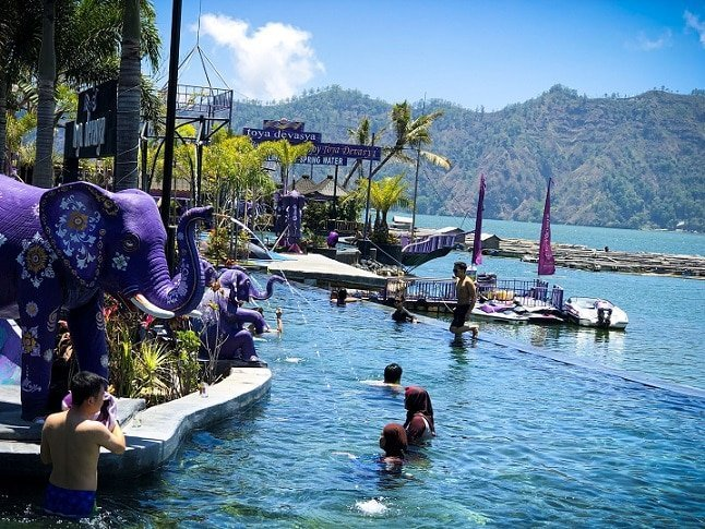 Swimmers in an infinity pool at Toya Devasya Bali hot springs. On the left are purple elephant fountain statues pouring water into the pool. In the background is Lake Batur, with hills in the far background.