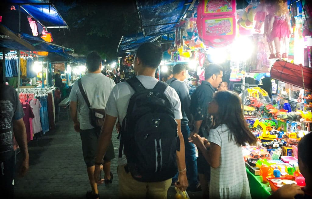 A man and child walking through a night market in Indonesia, traveling like a local
