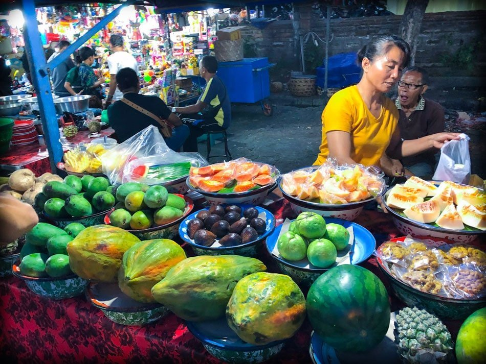 A fruit stand at a Bali night market in Gianyar, Bali in Indonesia. On display are papayas, watermelon, mangoes, oranges, and snake fruit.