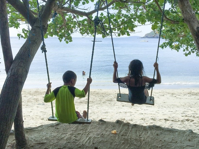 Children of a nomadic family swinging on a beach in Lombok, Indonesia