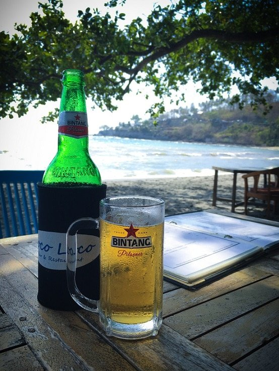 A bottle of Bintang beer with a glass of beer on a table at the beach, one of the popular things to do in Lombok.