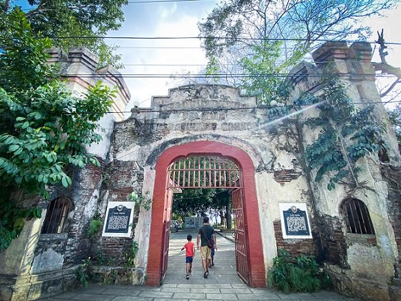 Visitors walking through the main gate of Plaza Cuartel in Puerto Princesa, Philippines