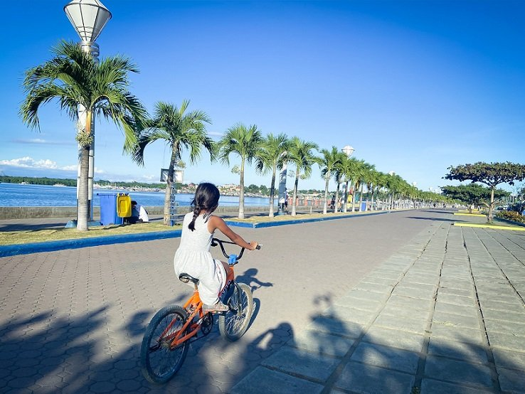 A child riding a bicycle along the Baywalk in Puerto Princes, Philippines while doing slow tourism