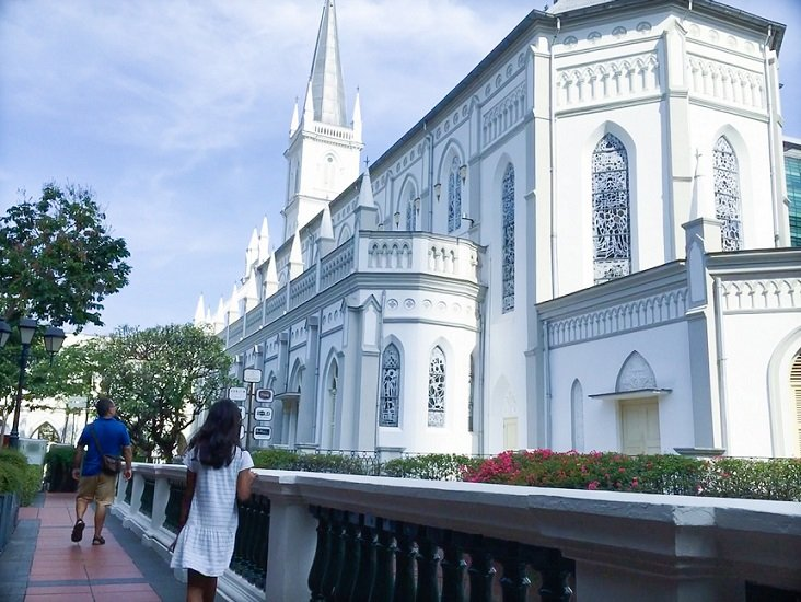 A man and girl walk by the former chapel at the Chijmes complex, one of the things to do in Singapore on a budget
