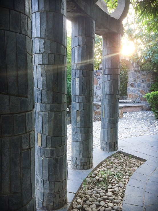 A sun flare behind stone columns at Garden of Five Senses in Delhi, India, where families can go during a visit to Delhi with kids