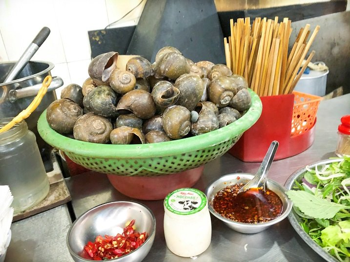 Snail shells in a basket on a metal counter serving food in Hanoi.